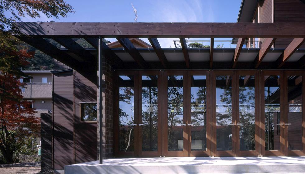 室内から連続するタイル貼のテラスと日除けの梁。 内と外の連続性とテラス下の落ち着きを与えます。